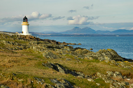 Picture of a lighthouse on a sea loch, mountains in the distance