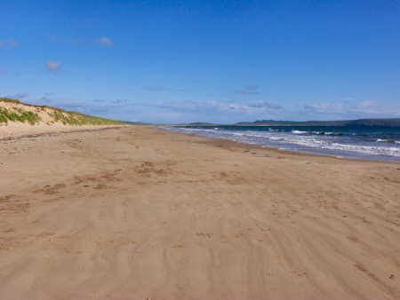 Picture of a beach with dunes behind it stretching into the distance