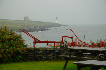 Picture of a view over a rain wet garden towards a lighthouse in the rain, grey clouds behind it