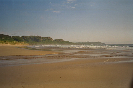 Picture of a beach in a bay with cliffs in the background, bathed in a golden sunshine