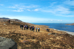 Picture of a group of walkers on a hill above a sea loch in brilliant sunshine