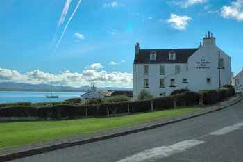 Picture of the Port Charlotte Hotel on Islay with the blue surface of Loch Indaal in the background