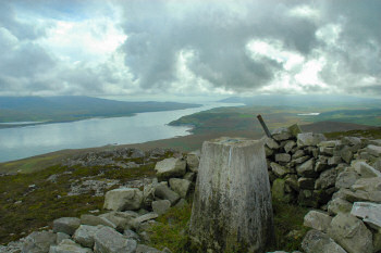 Picture of the summit of a hill (a marilyn) with a trig point and a view over a sound