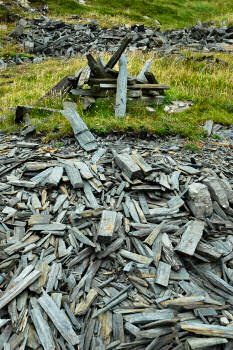 Picture of slate pieces in a disused quarry, some of it in a pile
