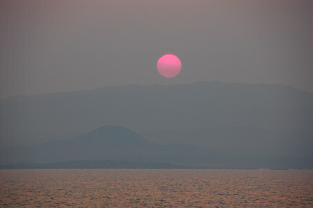 Picture of a red sun setting over a very hazy island
