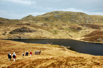 Picture of a group of walkers approaching a loch (lake) with a hill in the background