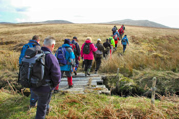 Picture of a group of walkers crossing a makeshift bridge into the open countryside