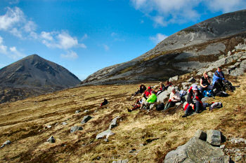 Picture of a group of walkers resting under a background of huge mountains (the Paps of Jura)