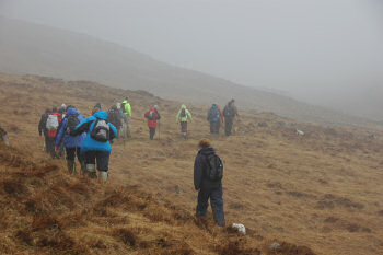 Picture of a group of walkers disappearing into the rain