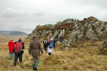 Picture of walkers climbing up to an old hillfort