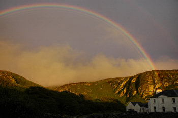Picture of a rainbow over crags and a house