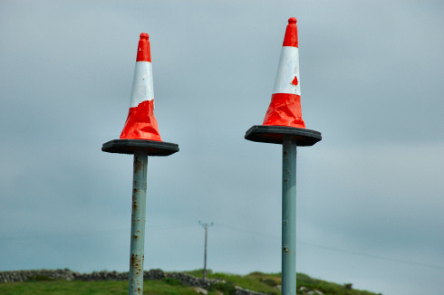 Picture of two traffic cones sitting on the top of two high poles