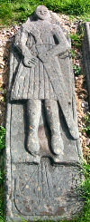 Picture of a grave slab of a warrior with his sword, carving of a birlinn at this feet