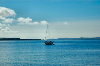 Picture of a sailing yacht anchored in a wide bay on a beautiful sunny day