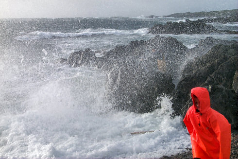 Picture of waves crashing over rocks, spray coming over. Also a boy in a red waterproof jacket