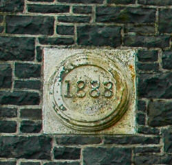 Picture of a plaque with the year 1888 in the wall of a building