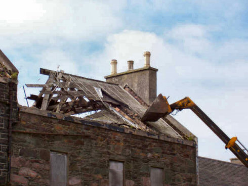 Picture of a digger taking down an old roof