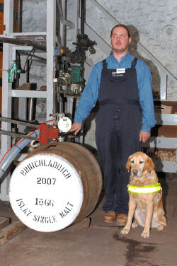 Picture of a man with his guide dog next to a whisky cask