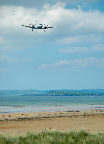 Picture of a plane coming in over a bay with a beach to land on an airport near the shore