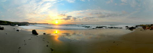 Picture of a panoramic view of a sunset over a sandy bay