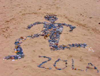 Picture of the image of a person created from stones in the sand, depicting a football player (Gianfranco Zola)