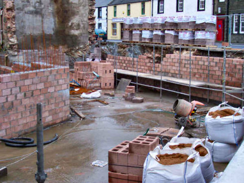 Picture of a building site, showing the basement, progress clearly visible