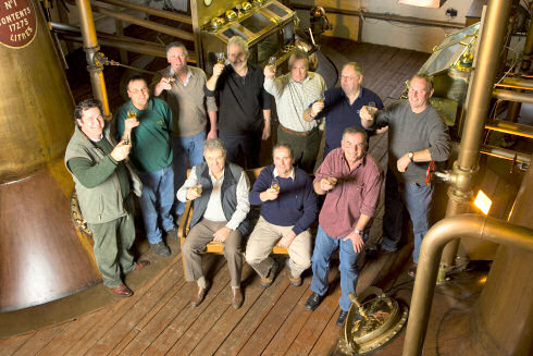 Picture of a group of people (farmers and whisky distillers) in a still house