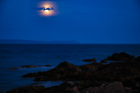 Picture of the moon shining over a sea loch, another part of the island on the other side of the loch