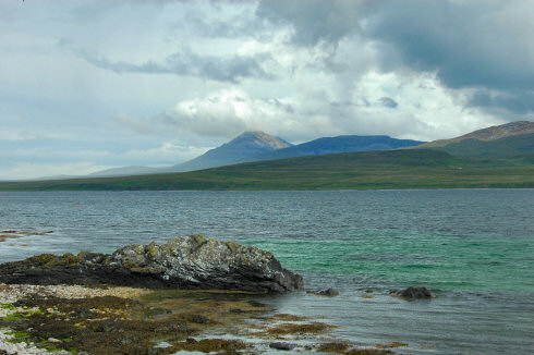 Picture of a view over a sound between two island, a large mountain on the other island