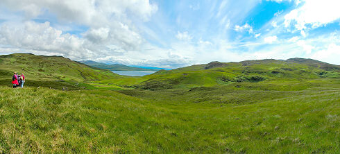 Picture of a panoramic view over a wide glen with a sound between two island at the end