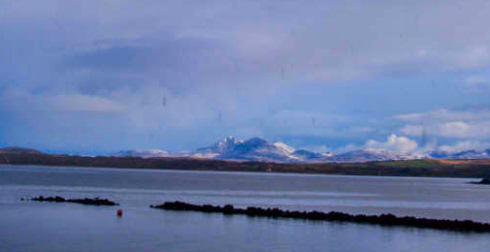 Picture of snow covered mountains seen in the distance across a sea loch and some lower hills