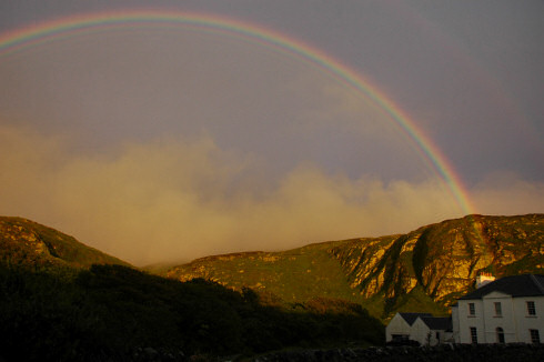 Picture of a rainbow over some rocky crags and a house