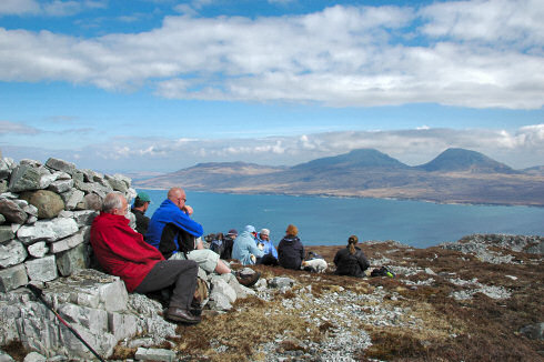 Picture of a group of walkers resting on the top of a hill looking over a sound to another island (from Islay to Jura)
