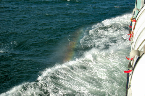 Picture of a small rainbow visible in the spray of the bow wave of a ship