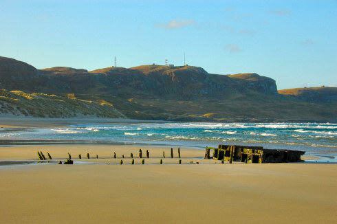 Picture of a ship wreck on a beach, crags in the background