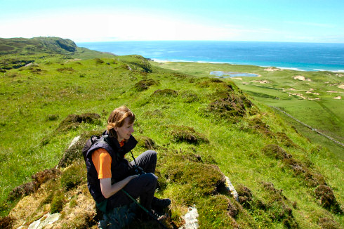 Picture of a young woman sitting on hills high above dunes and the sea
