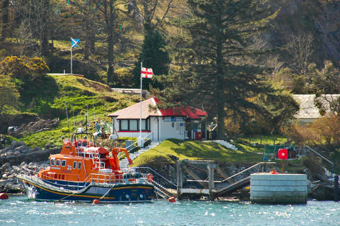 Picture of a RNLI station with a lifeboat anchored in front of it