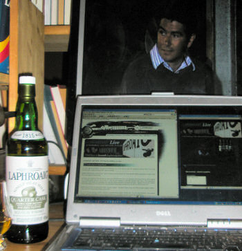 Picture of a laptop and an external monitor set up to watch the Laphroaig Live webcast, John Campbell on screen