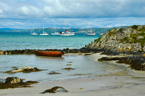 Picture of a beach with a rowing boat and a few sailing yachts moored out at sea