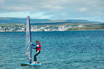 Picture of a windsurfer on a sea loch, the village of Bowmore in the background