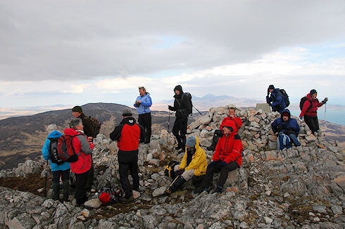 Picture of a group of walkers at the summit cairn and trigpoint of Beinn Bheigier on Islay