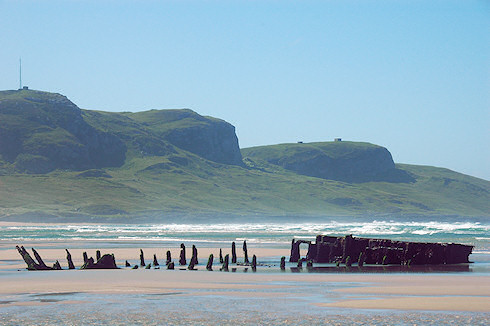 Picture of a wreck on a beach on the Isle of Islay with the Kilchoman Crags in the background