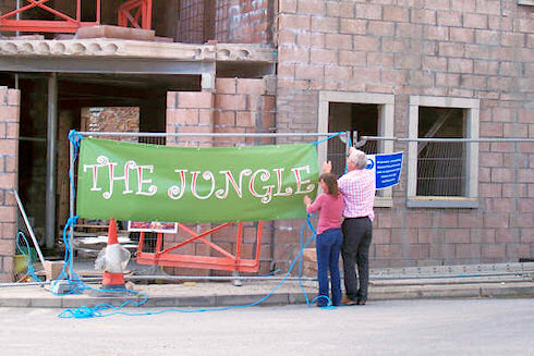 Picture of two people next to a banner reading The Jungle