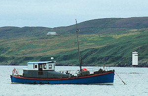 Picture of an old lifeboat now used as a pleasure boat, moored with a lighthouse in the distant background