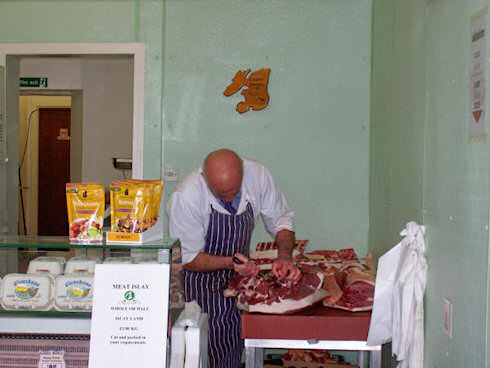 Picture of a butcher de-boning a pig