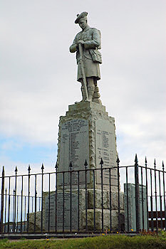 Picture of the war memorial in Port Ellen, Islay. Statue of a soldier on top of a plinth with the names of the fallen