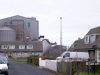 Picture of a road with house before an industrial maltings with a collapsed silo