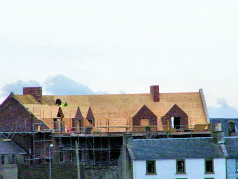 Picture of the back of an under construction hotel with the roof nearing completion