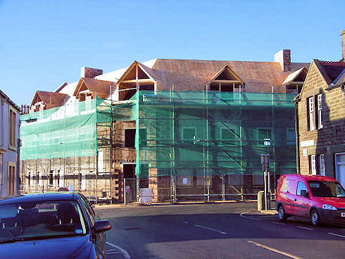 Picture of the front of an under construction hotel with the roof nearing completion