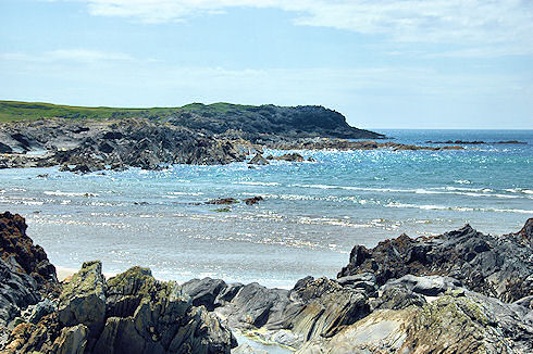 Picture of a mostly rocky bay with only a few small waves coming in